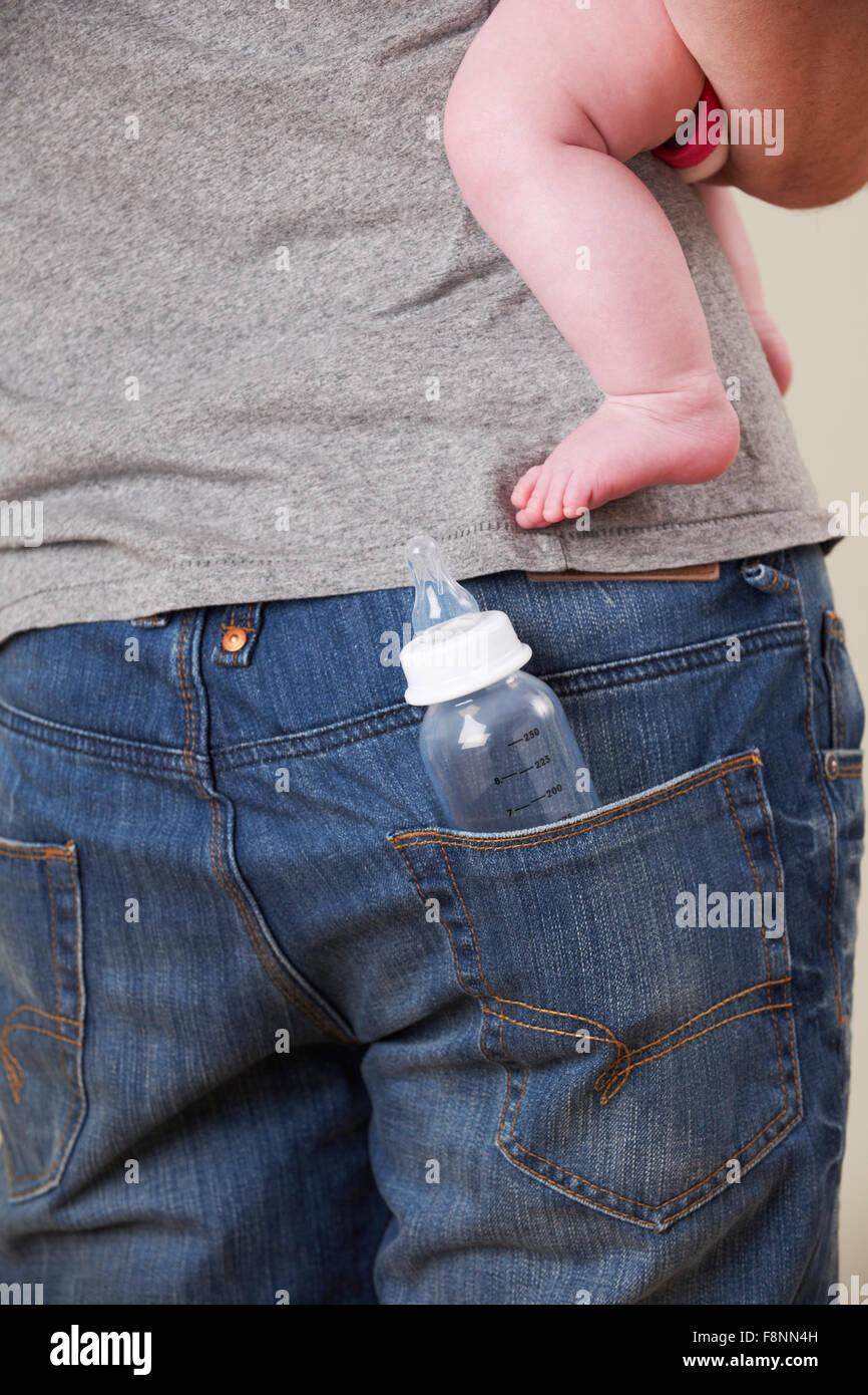 Vista posterior del padre llevar a bebé con biberón en el bolsillo Imagen De Stock