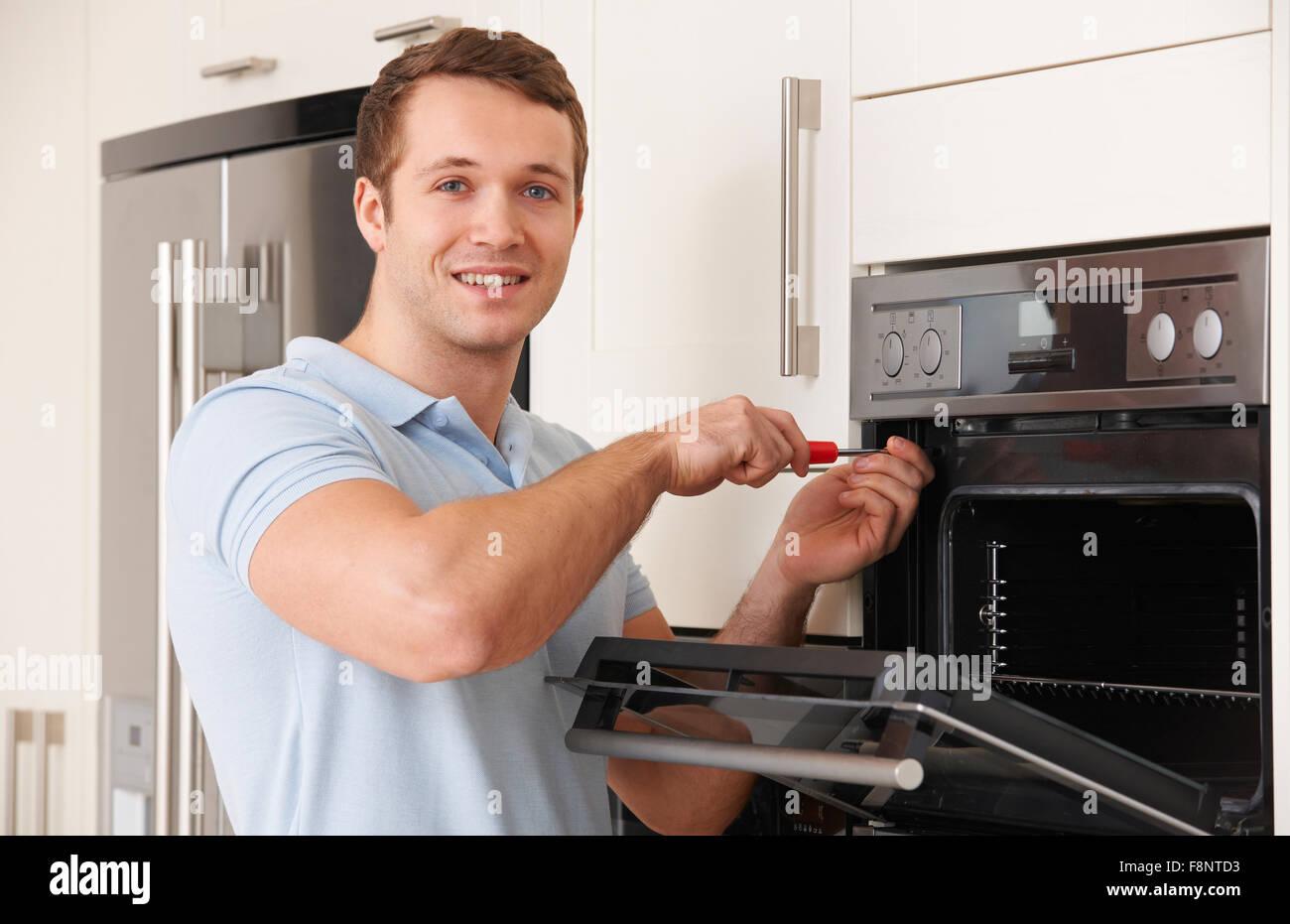 Hombre reparando en cocina horno doméstico Imagen De Stock