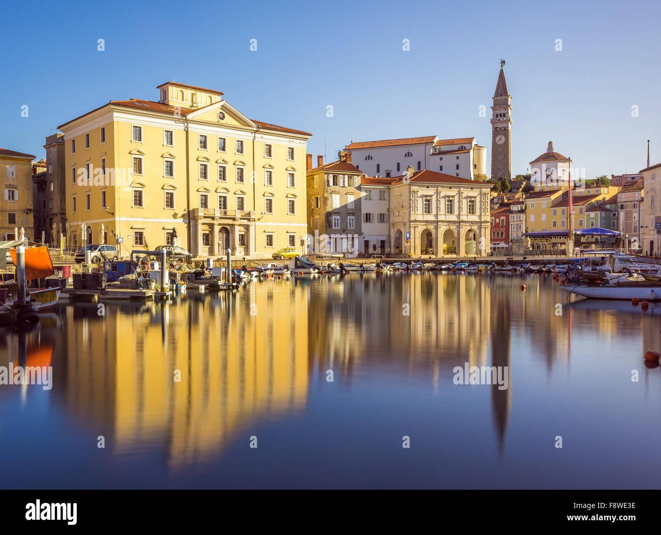 Edificios de la plaza principal de Tartini Piran ciudad reflejada en el agua en Eslovenia. Foto de stock
