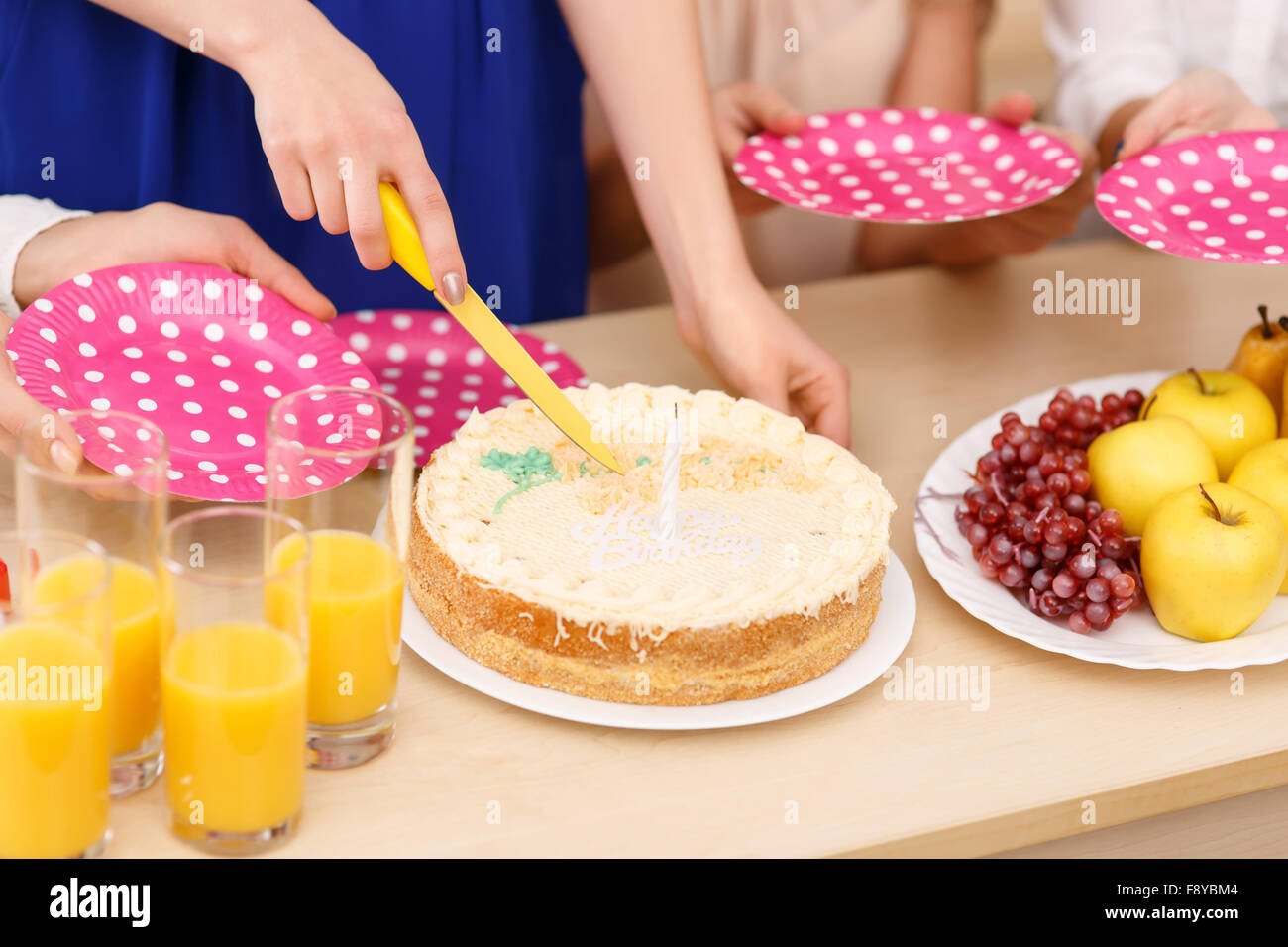 Las niñas están a punto de compartir una tarta de cumpleaños. Imagen De Stock
