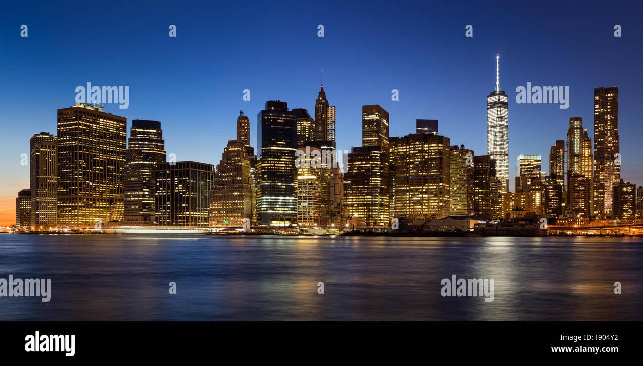 La Ciudad de Nueva York de Manhattan, el Distrito Financiero al atardecer con rascacielos iluminados elevándose Imagen De Stock