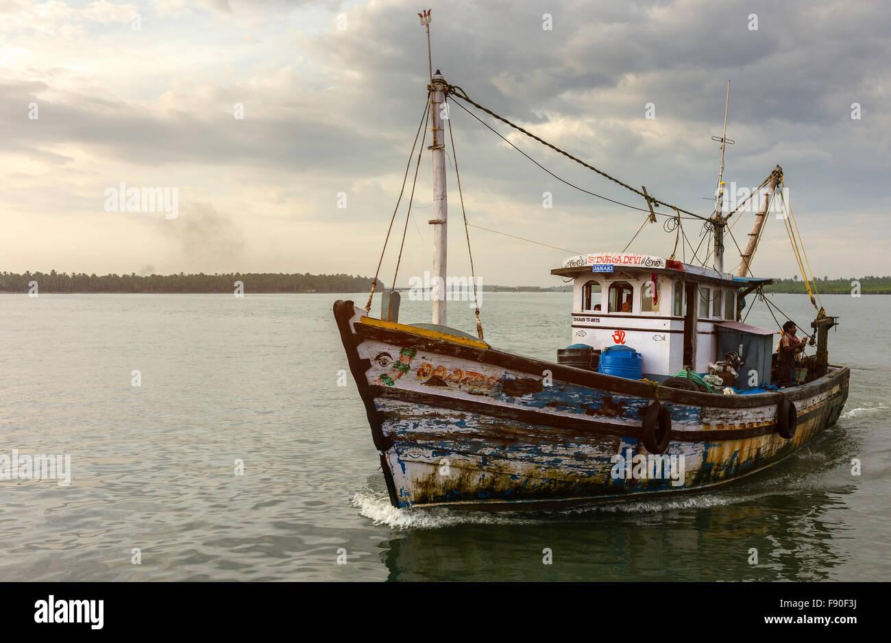 Arrastrero devuelve al atardecer desde el mar profundo viaje de pesca en el Mar de Arabia y el ancla en puerto Valapattam, Kerala, India. Foto de stock