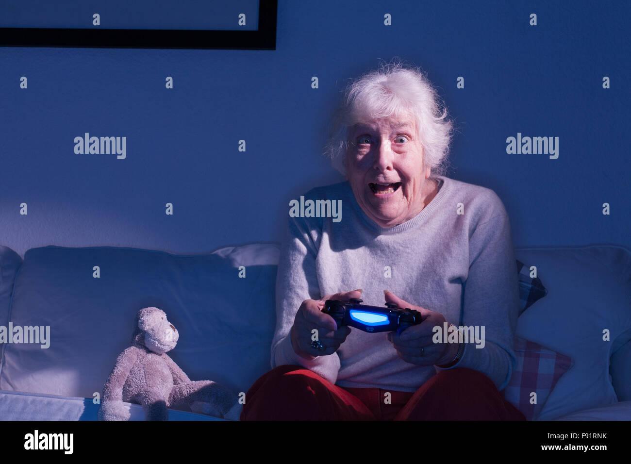 Anciana sentada en un sofá jugando en una Playstation 4 junto a un mono de peluche. Foto de stock