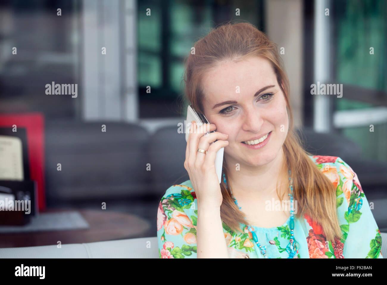 Mujer hablando por teléfono en la cafetería Imagen De Stock