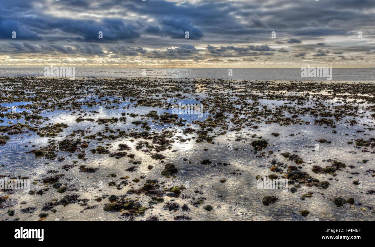 Concepto de tranquilidad. Playa por el mar en una marea baja, con reflejos del cielo en el agua restante. Foto de stock