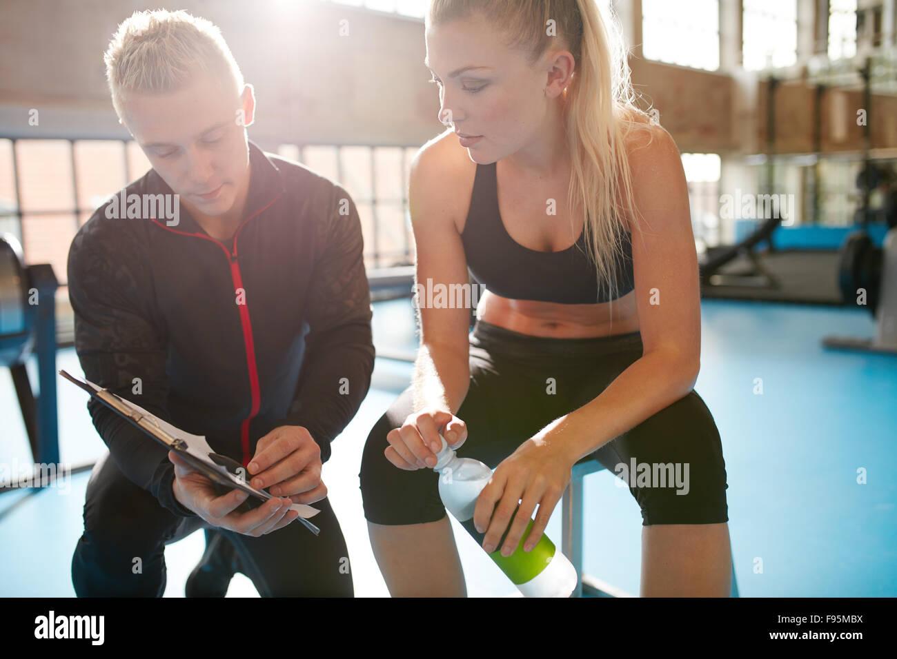 Foto de un entrenador personal ayudando a un miembro de gimnasio con su plan de ejercicio. Formador pasa por plan Imagen De Stock