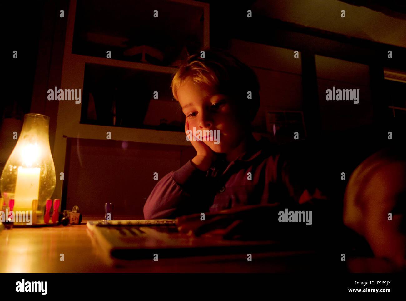 Un niño lee a la luz de las velas justo antes de cama-tiempo. Foto de stock
