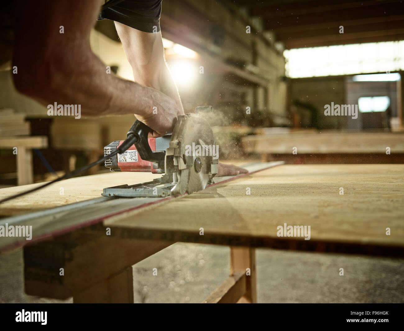 Carpintero aglomerado de corte con una sierra circular, Austria Foto de stock