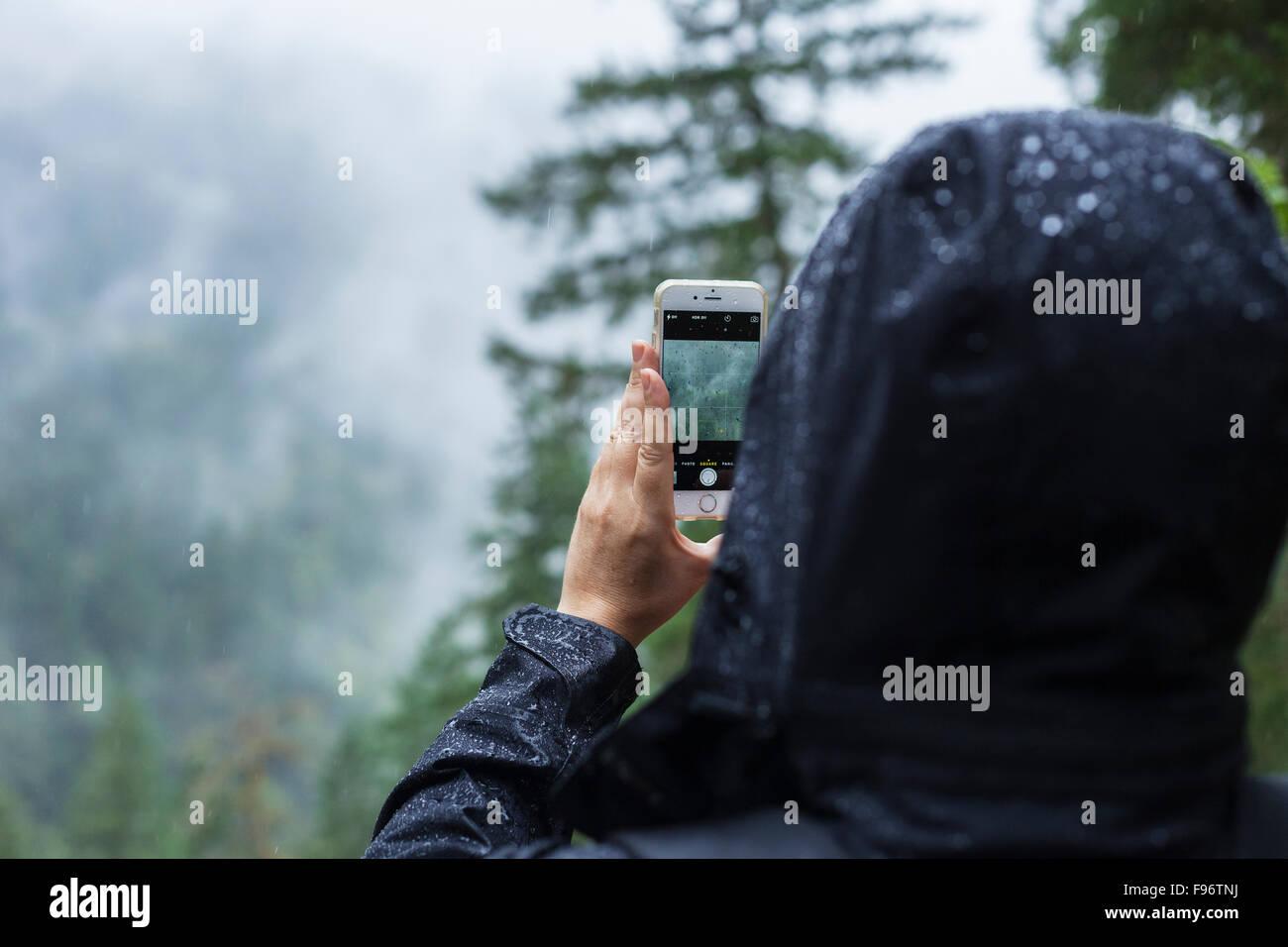 Mujer toma la fotografía en la lluvia, BC, Canadá Foto de stock
