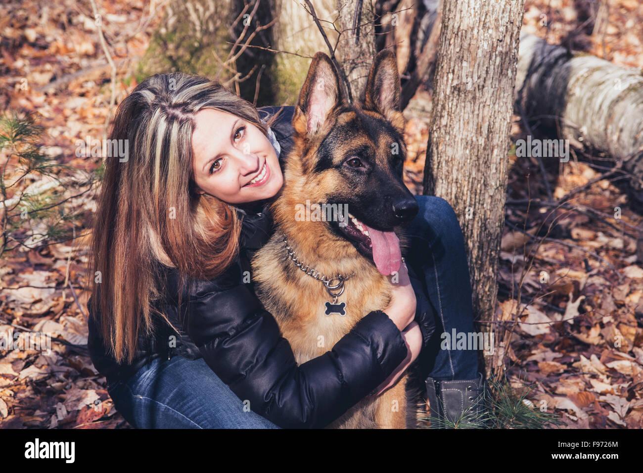 Mujer joven sonriente con un perro pastor alemán al aire libre en el bosque Imagen De Stock