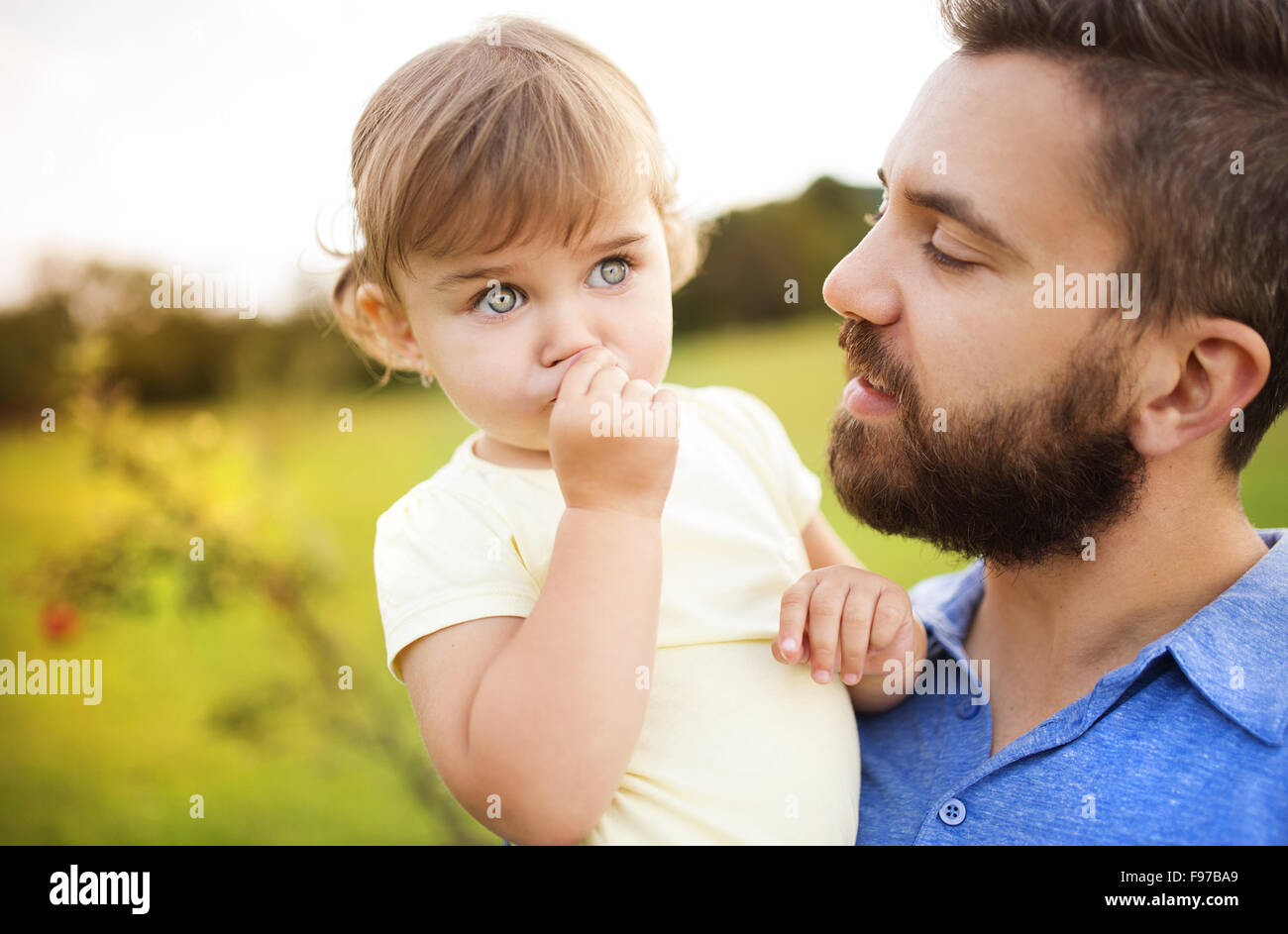 Hipster padre jugando con su hija en el parque verde. Imagen De Stock