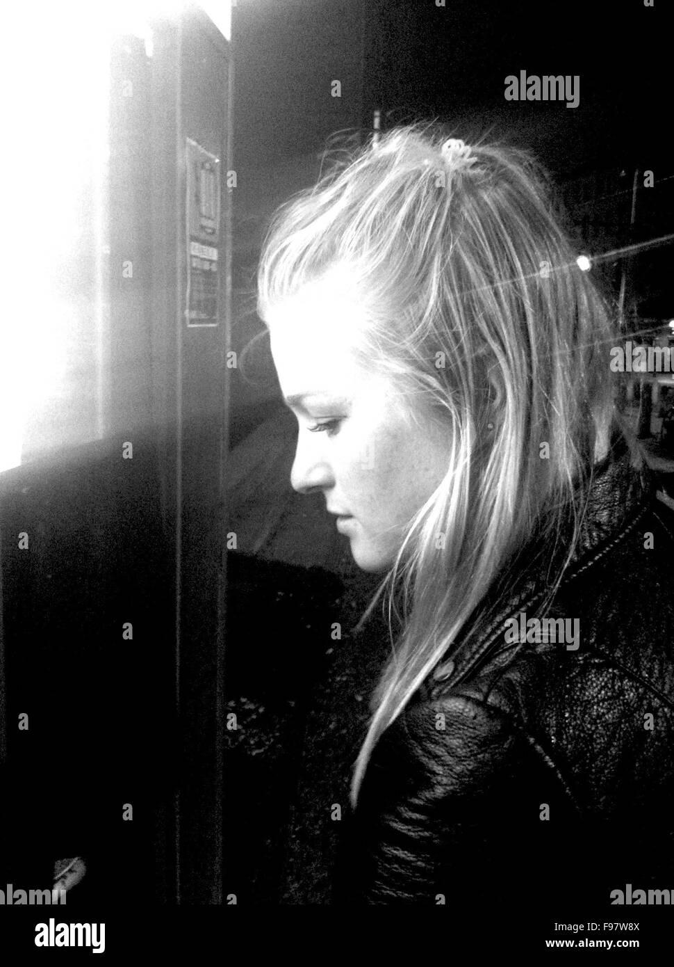 Ver perfil de Mujer de pie por la máquina de billetes por la noche Imagen De Stock