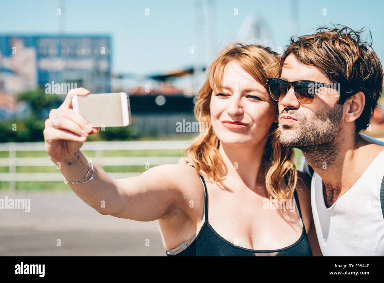 Feliz amigos haciendo clic en Selfie teléfono inteligente mientras está parado afuera Imagen De Stock