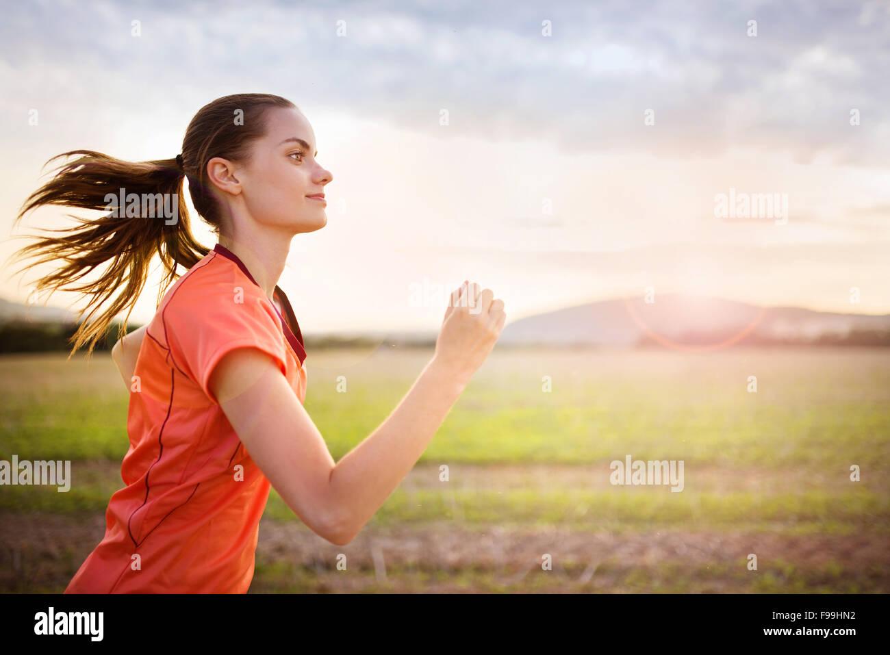 Cross-country trail running mujer al atardecer. Ejercicio Runnerwoman fuera como parte de un estilo de vida saludable. Imagen De Stock