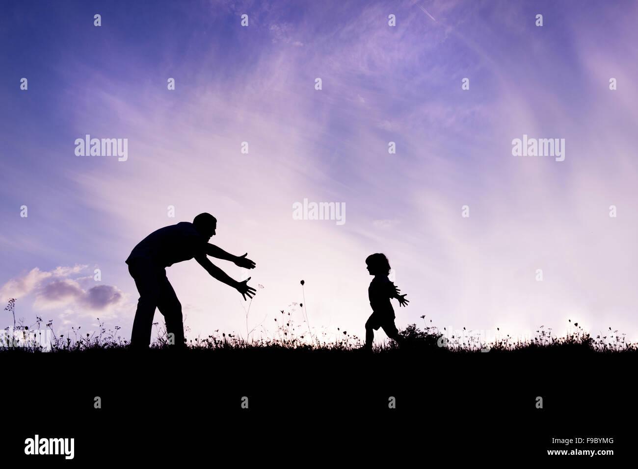 Silueta de padre feliz divirtiéndose con su hijo Foto de stock