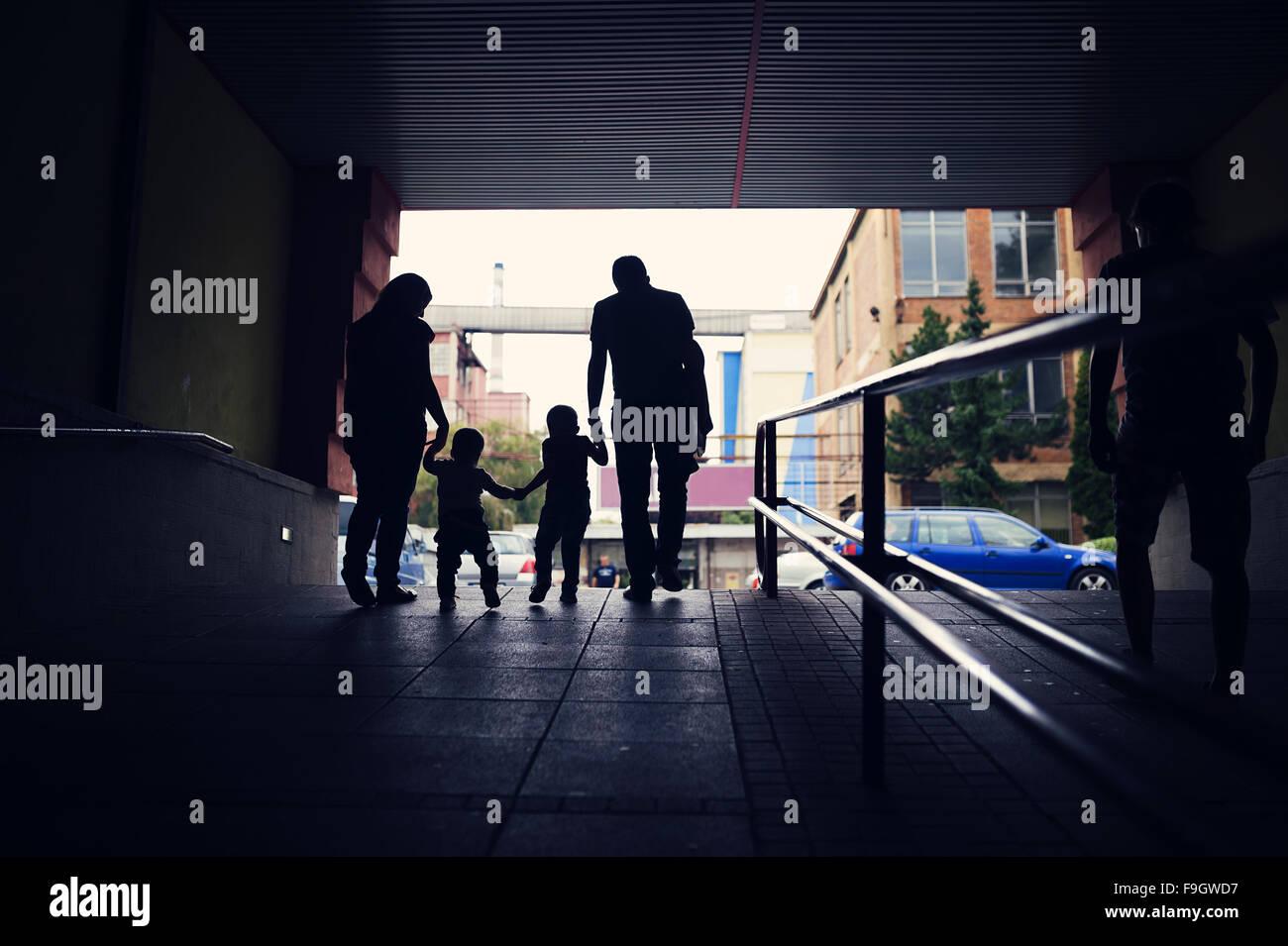 Una familia joven con dos chicos en una boca de metro. Imagen De Stock