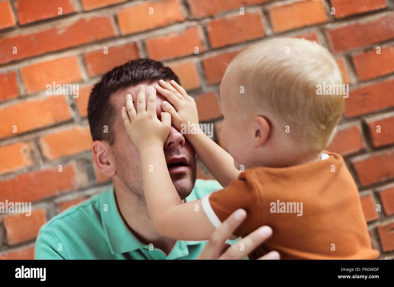 Padre e hijo haciendo muecas juntos sobre un fondo de pared de ladrillo Imagen De Stock