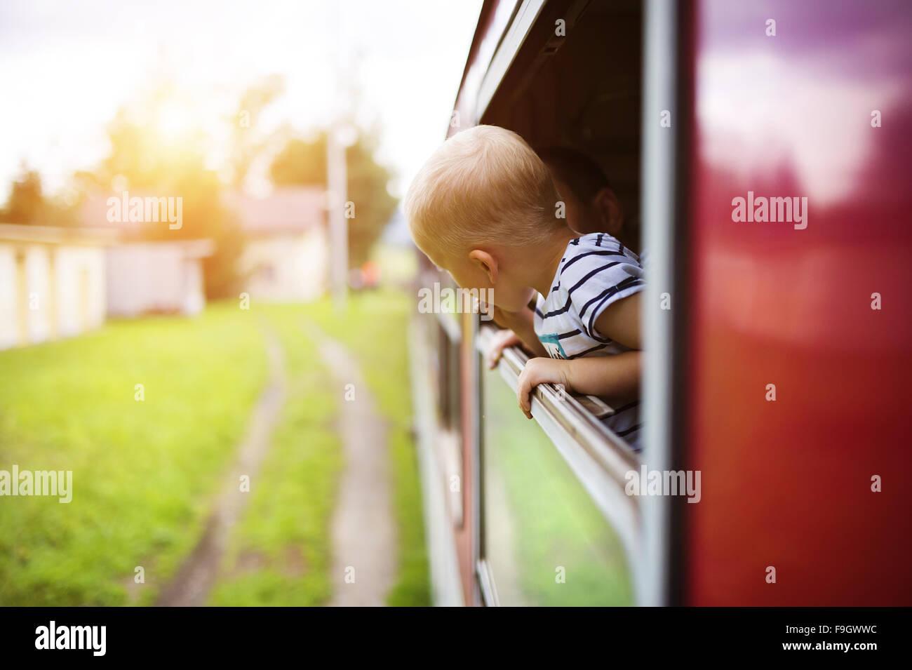 Niñito viajar en tren mirando fuera de la ventana. Imagen De Stock