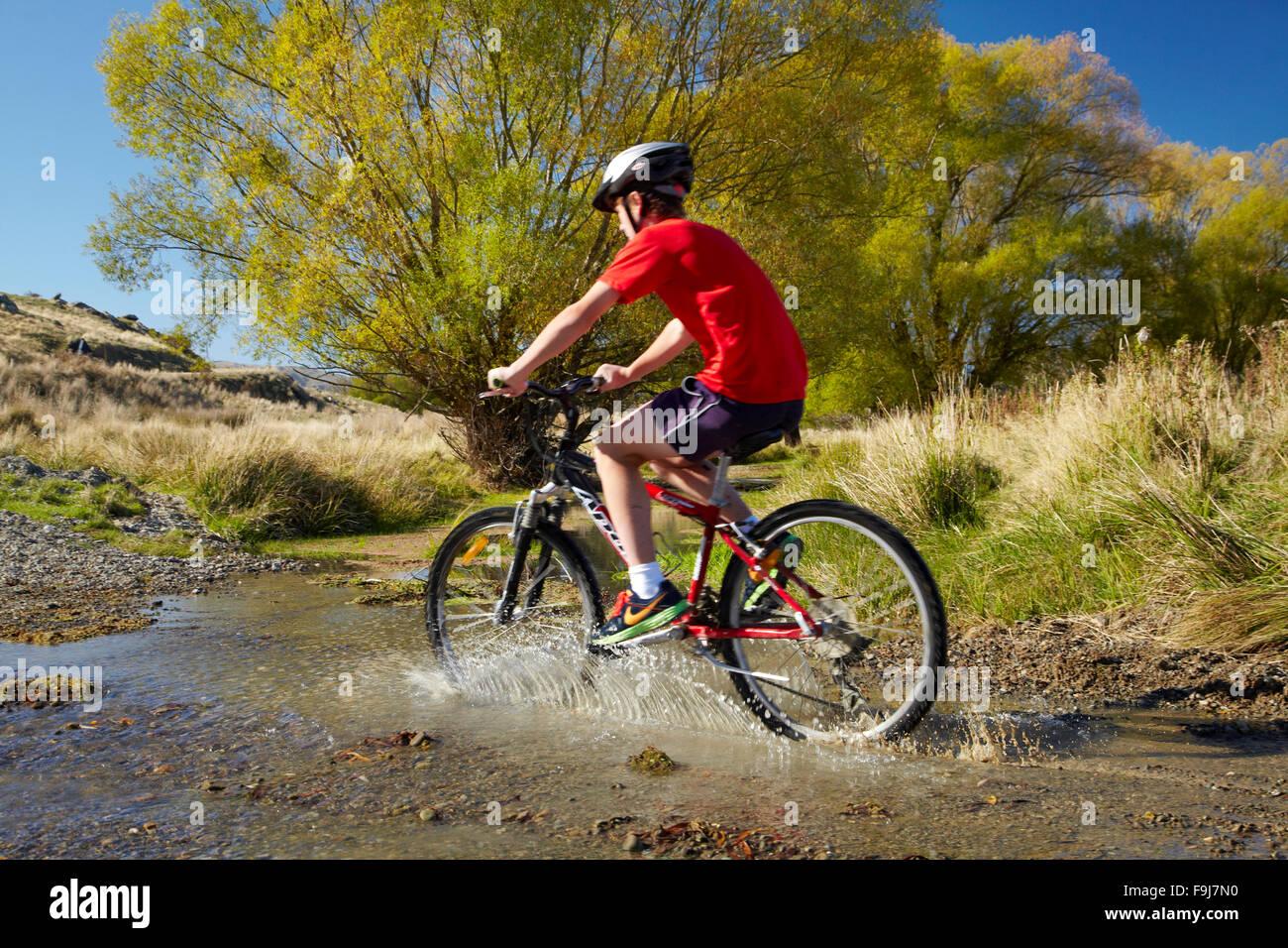 Ciclista cruzar el arroyo, quemadura Ida Ida Valley, junto a Otago Central Rail Trail, Central Otago, Isla del Sur, Imagen De Stock