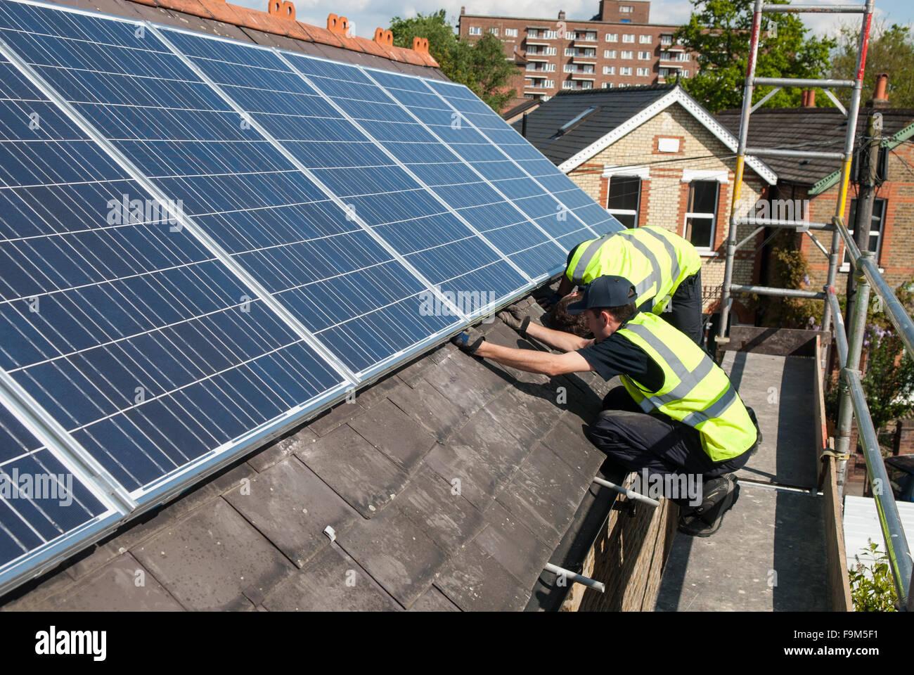 Los trabajadores instalar paneles solares fotovoltaicos en el tejado de pizarra de una casa victoriana en Londres, Imagen De Stock