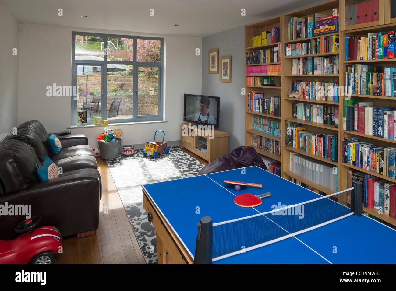 Playroom mostrando mesa de tenis de mesa, estanterías con libros y juguetes en un moden casa familiar. Imagen De Stock
