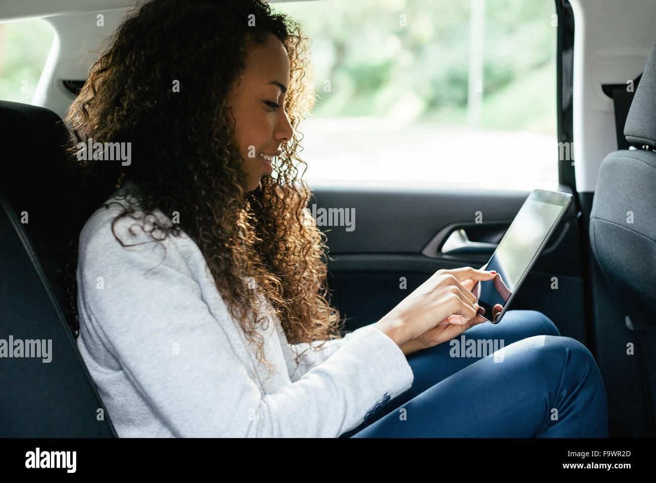 Mujer joven sentada en el asiento de atrás de un coche con mini tablet Imagen De Stock