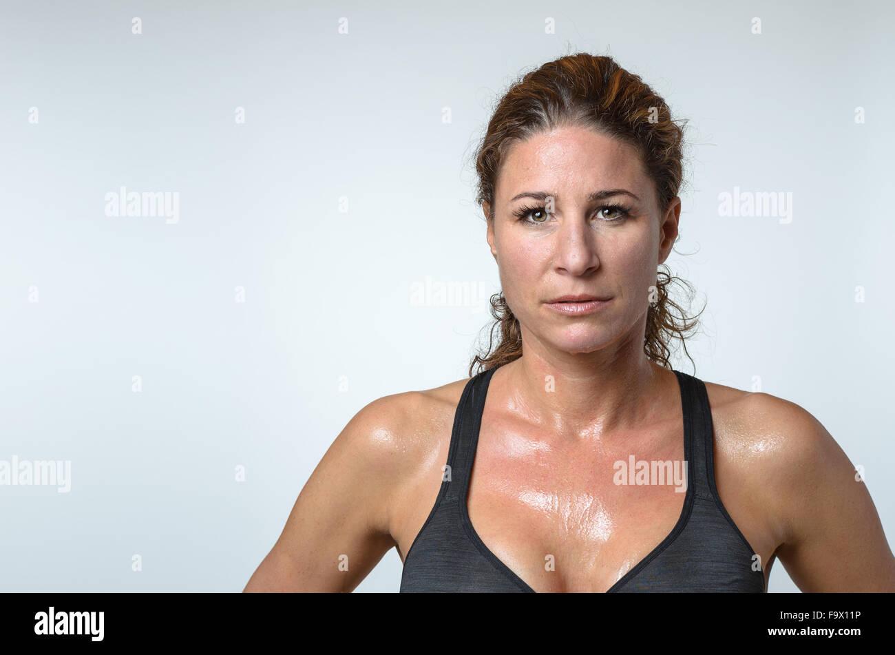 Sudorosos atléticos atractivo colocar joven con una pátina de sudor sobre su piel y precioso pelo rizado Imagen De Stock