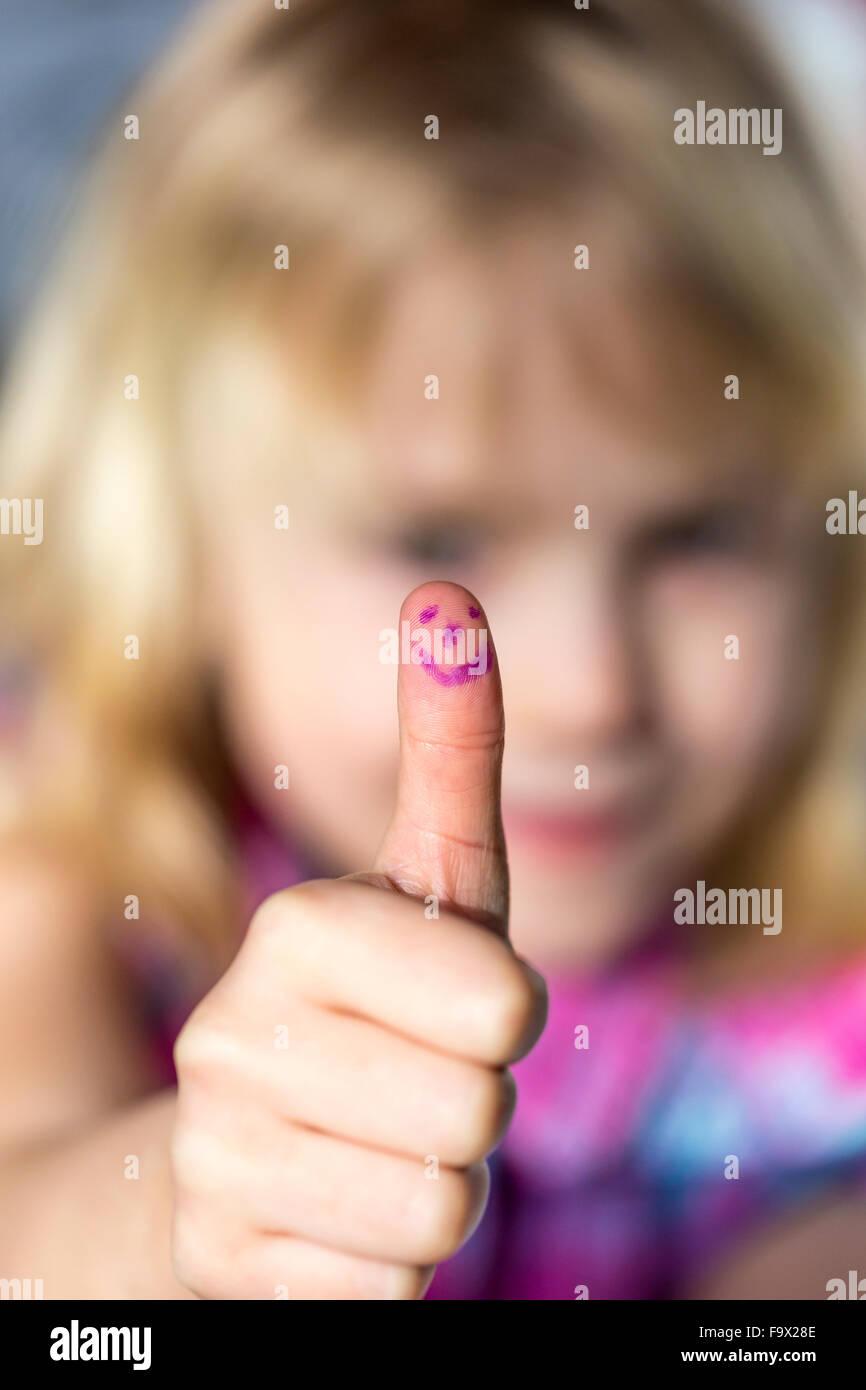 Niña mostrando pulgar arriba con cara sonriente Imagen De Stock
