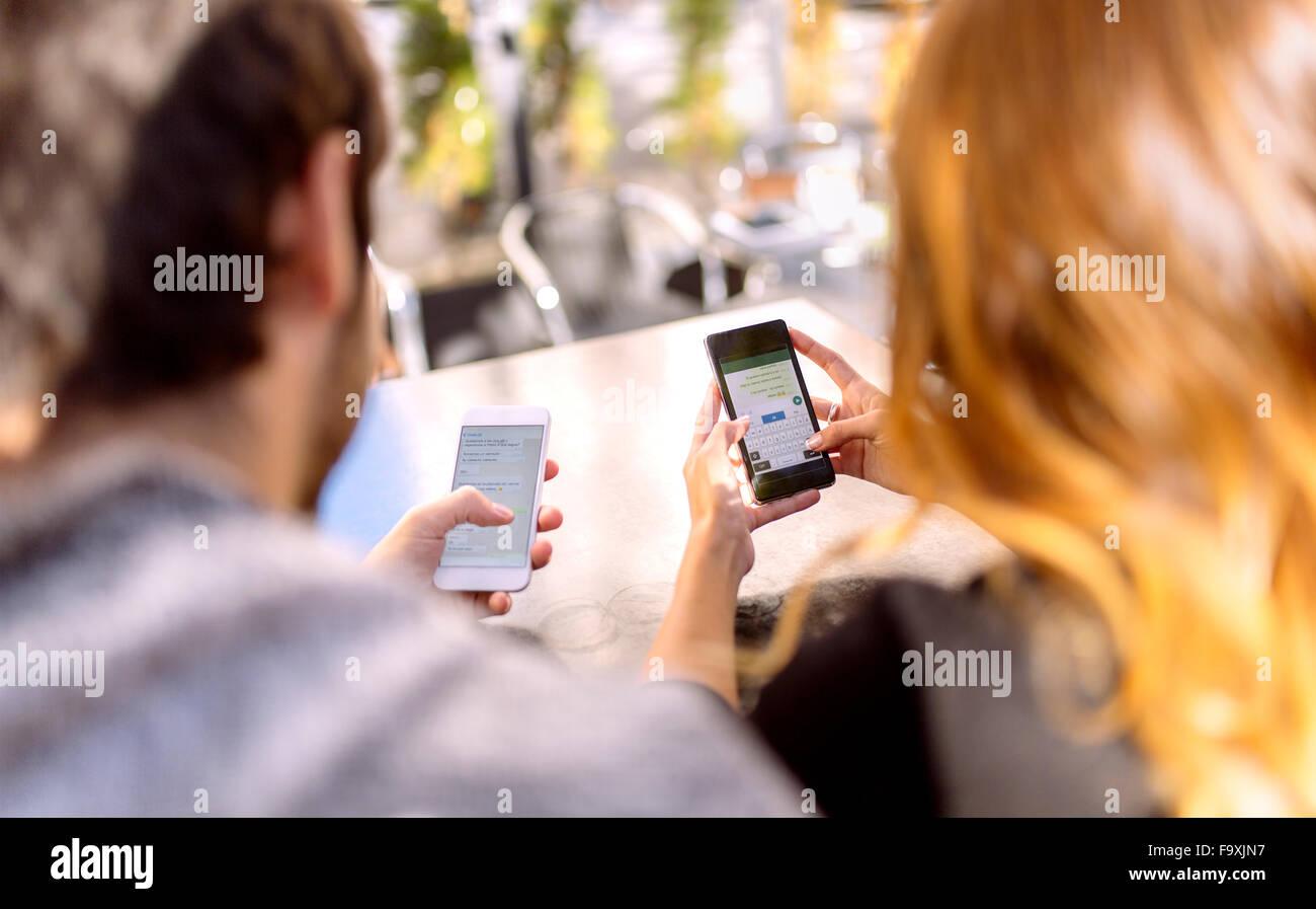 Vista posterior de la joven pareja sentada al lado de la otra, usando sus teléfonos inteligentes Imagen De Stock