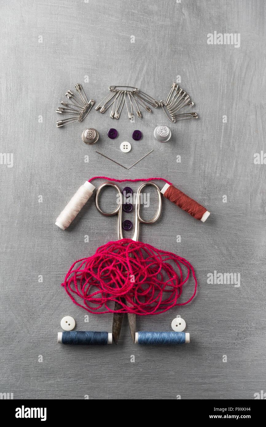 Construcción de elementos de costura de figur una chica sonriente sobre fondo gris Imagen De Stock