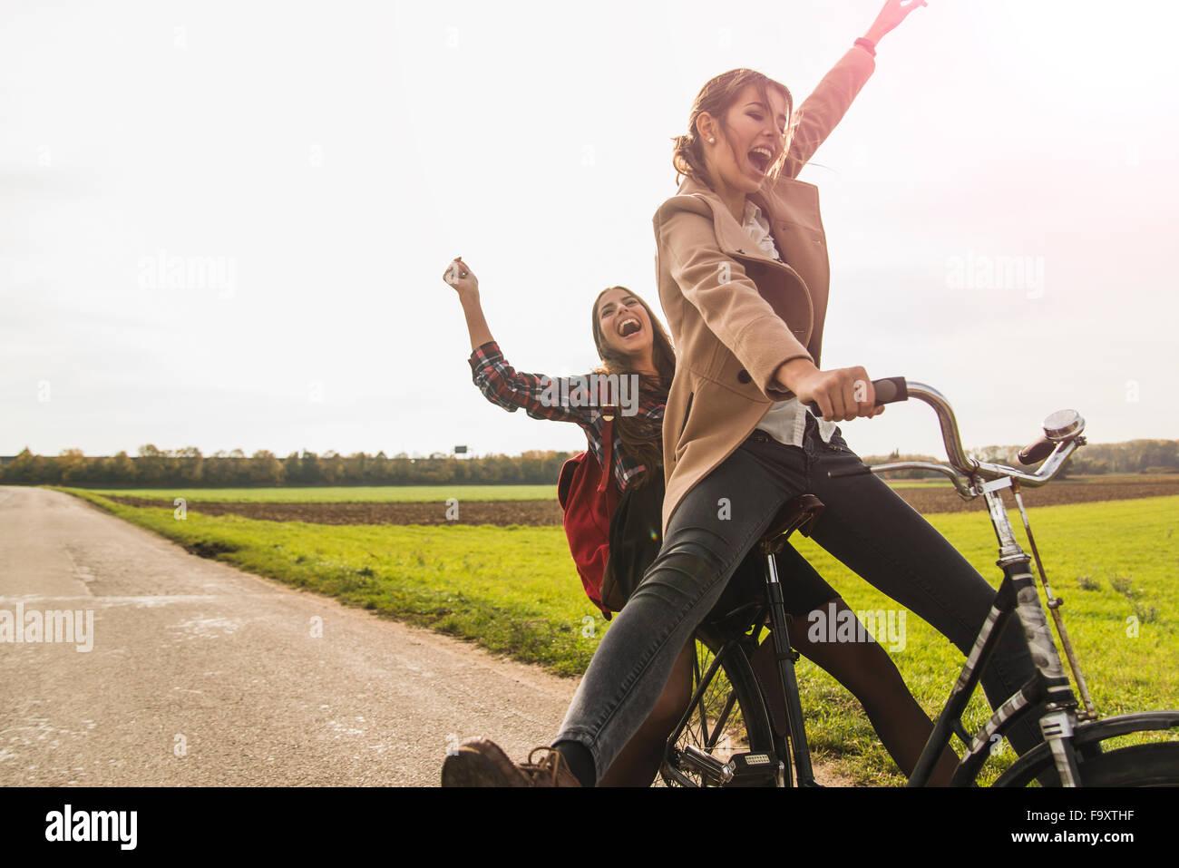 Dos Exuberantes Mujeres Jóvenes Compartiendo Una Bicicleta