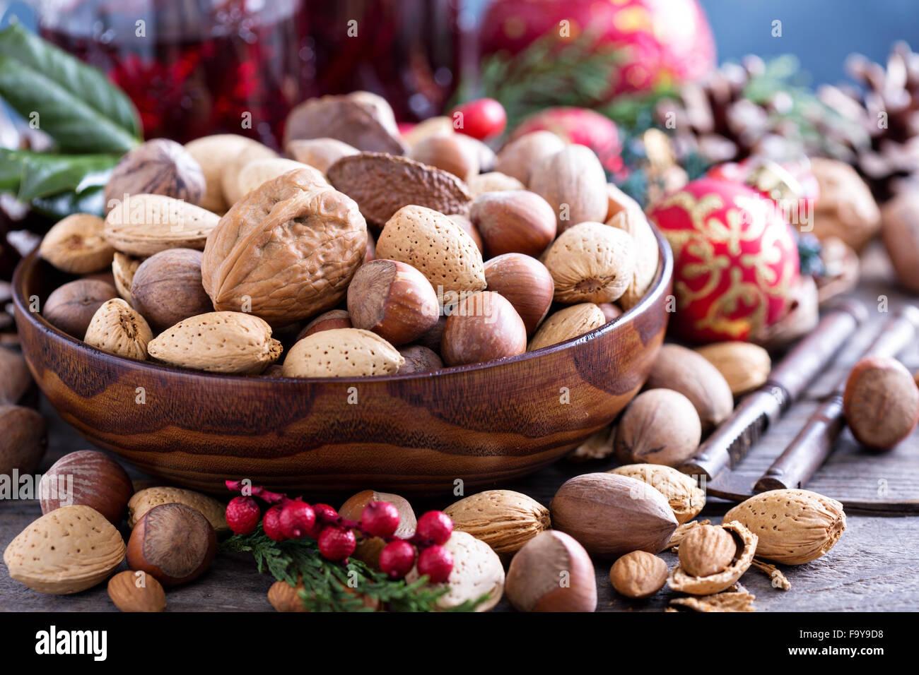 Variedad de nueces con cáscara en un recipiente marrón Foto de stock