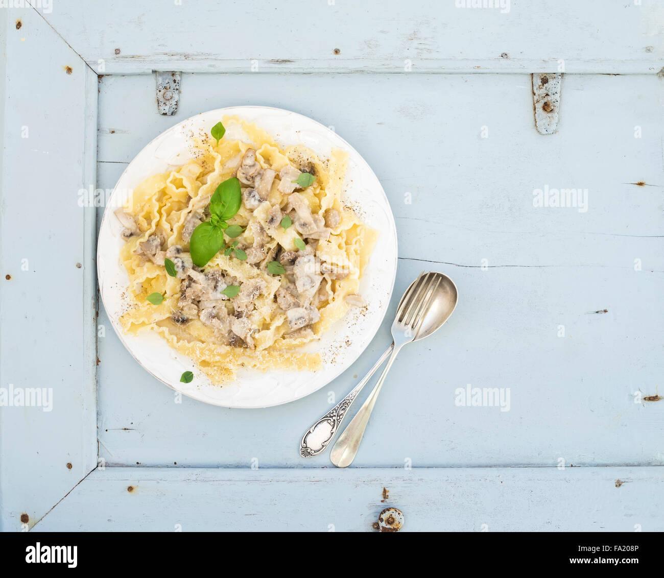 Pasta mafaldine con champiñones y salsa de nata en placa de cerámica blanca sobre fondo azul de madera. Imagen De Stock