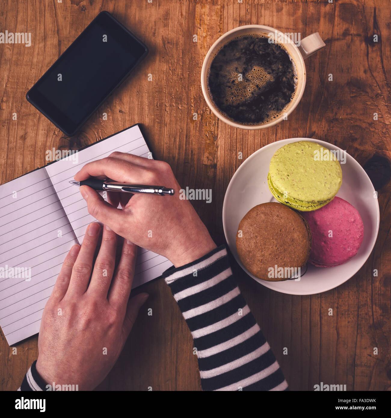 Mujer escribiendo en el portátil durante el desayuno, vista superior de manos femeninas con lápiz, taza de café, teléfono móvil y macaron cookie Foto de stock