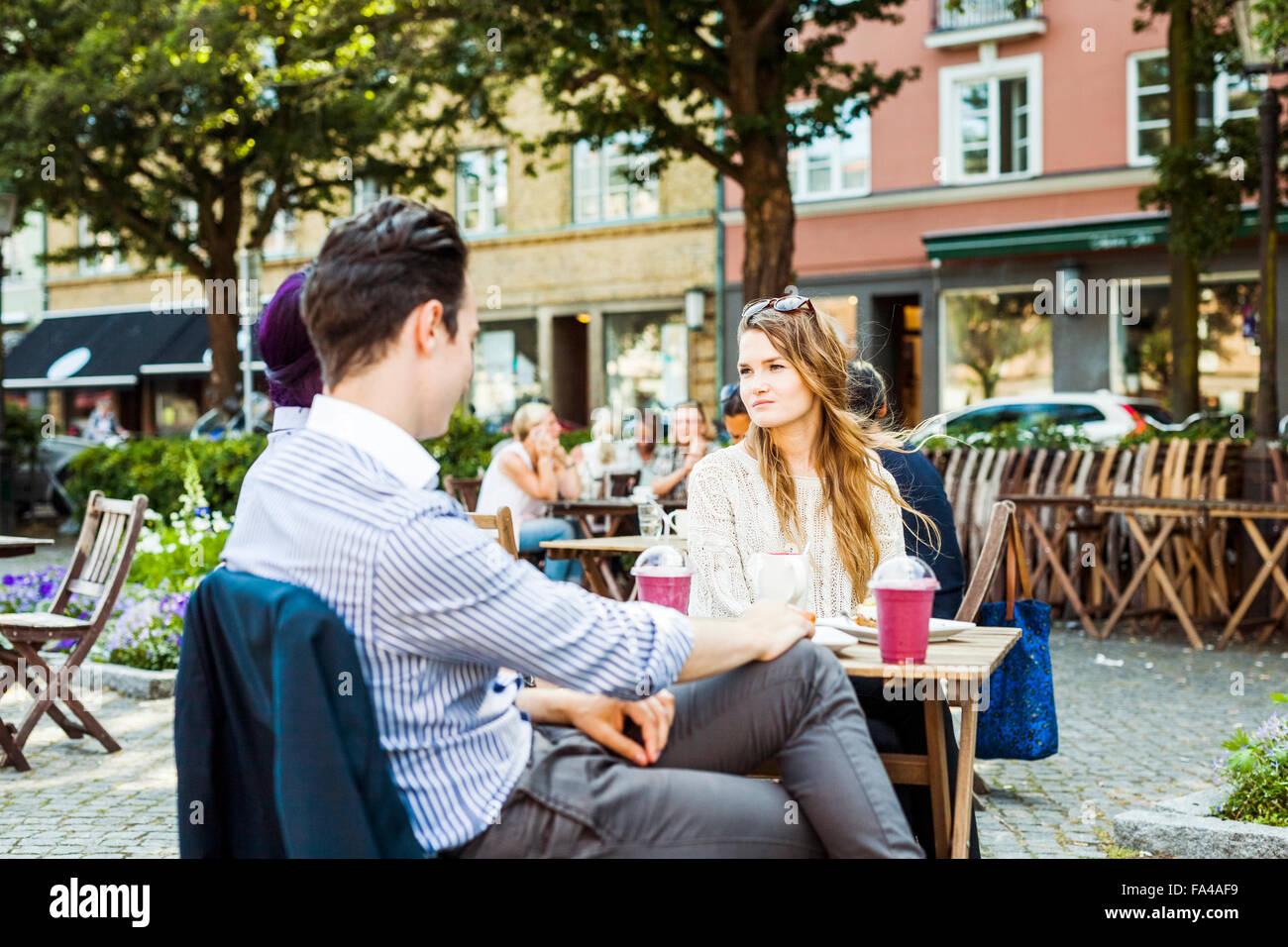 Amigos sentado en la cafetería en la plaza de la ciudad Imagen De Stock