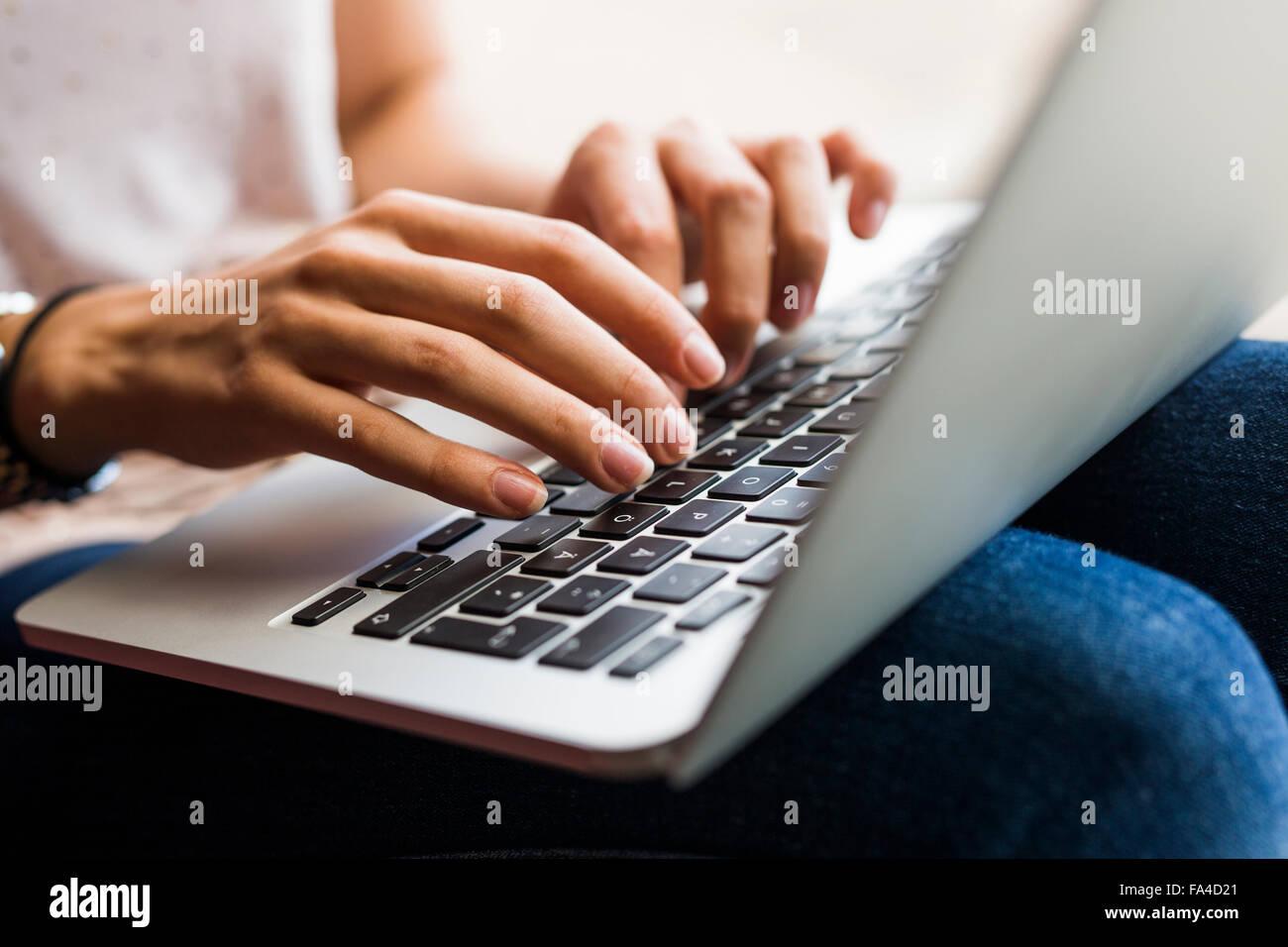 Sección media de la moda modelo usando un portátil en studio Imagen De Stock