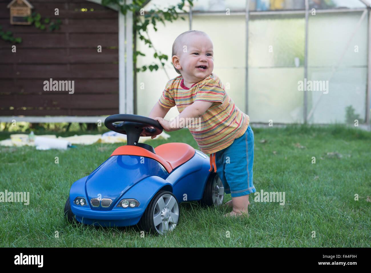 Baby Boy con su coche de juguete y llorando en el césped, Munich, Baviera, Alemania Foto de stock