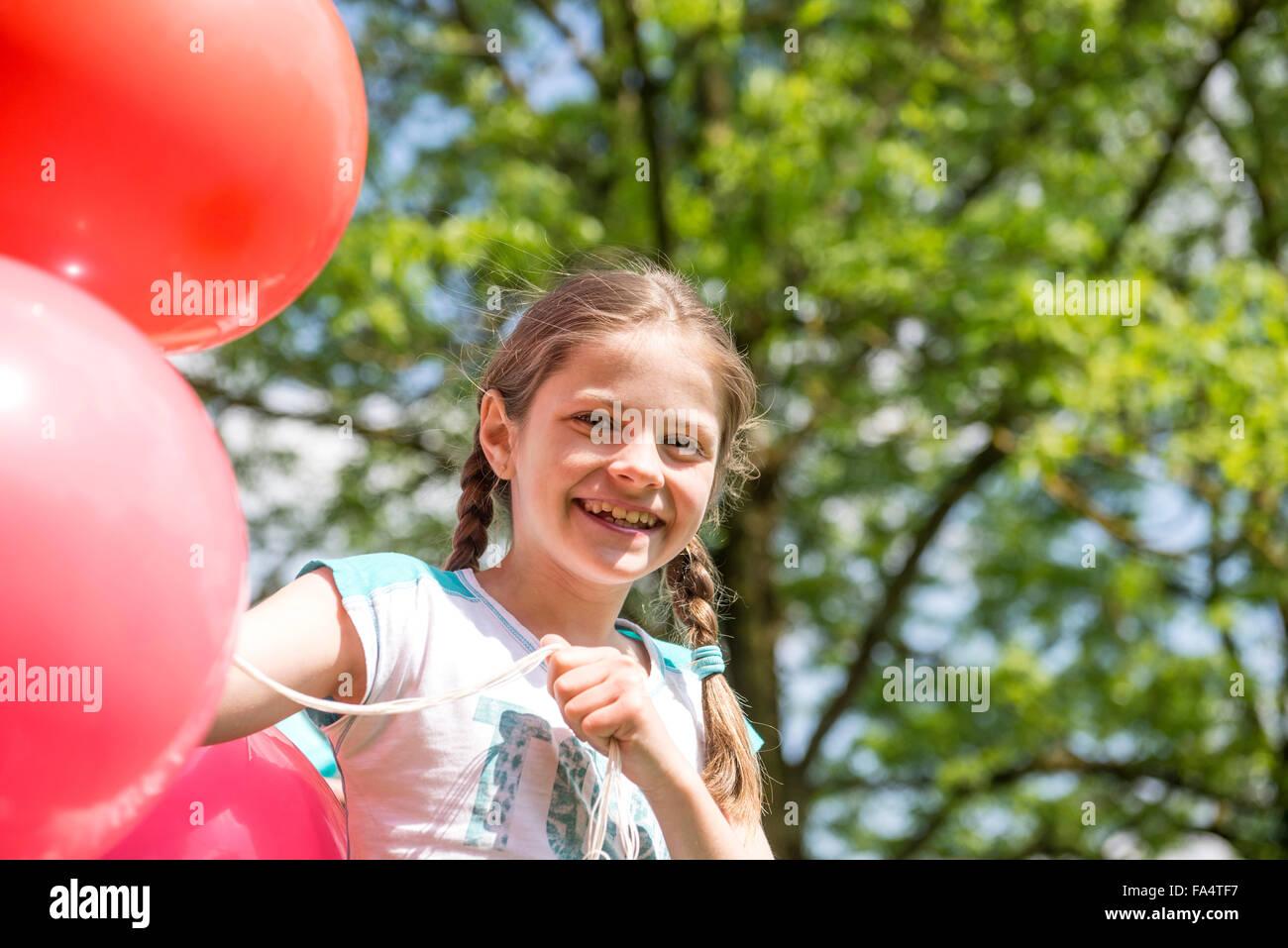 Retrato de una niña sonriente sosteniendo globos rojos, Munich, Baviera, Alemania Imagen De Stock