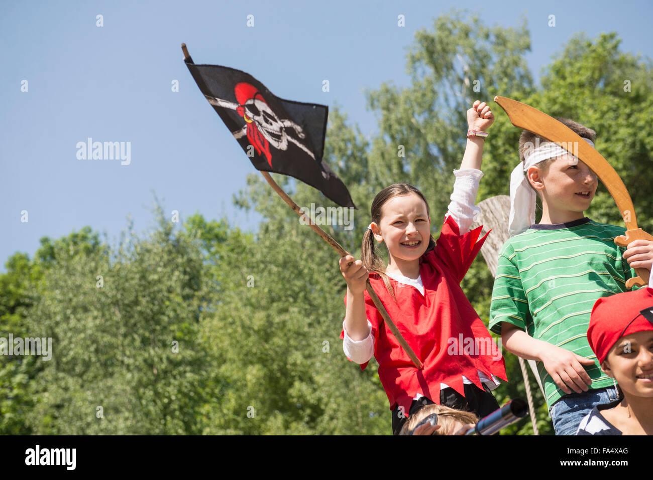 Chica sujetando la bandera pirata con sus amigos en juegos de aventura, Baviera, Alemania Imagen De Stock