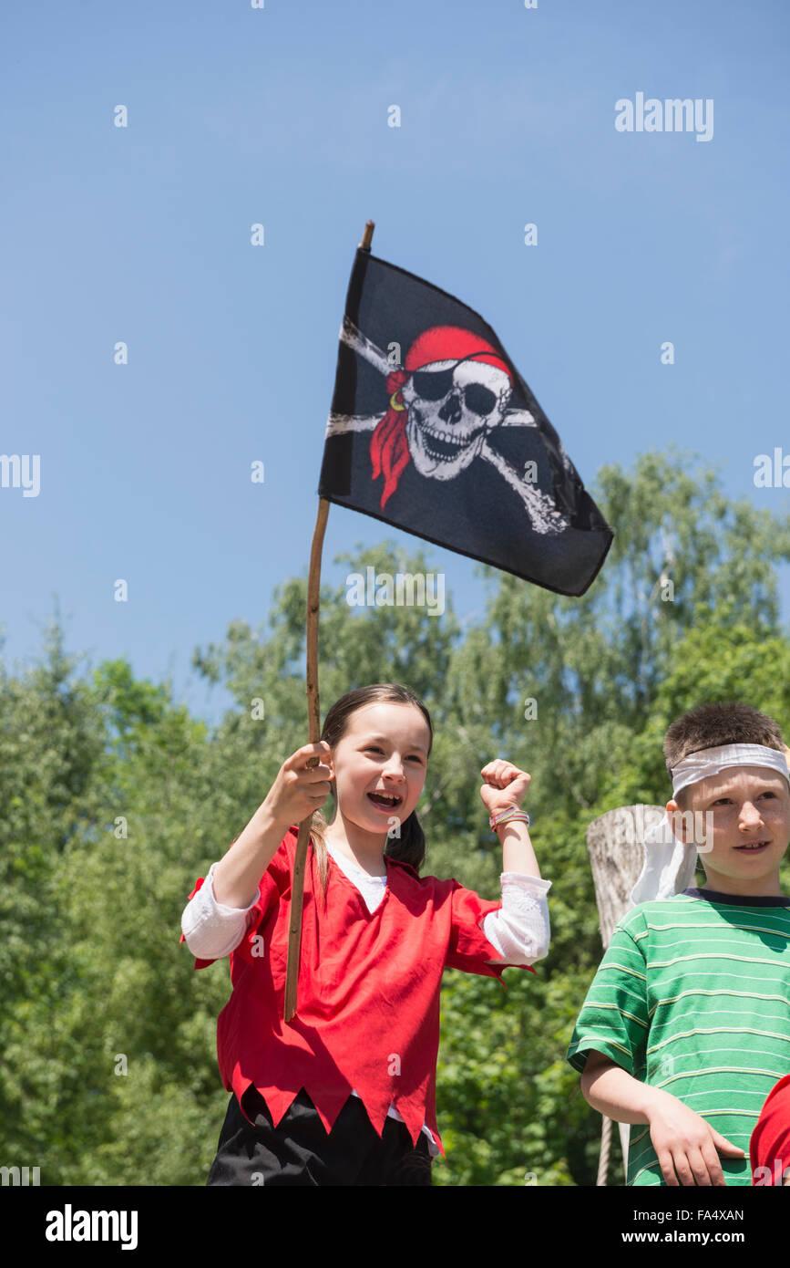 Chica sujetando la bandera pirata con una amiga en juegos de aventura, Baviera, Alemania Imagen De Stock