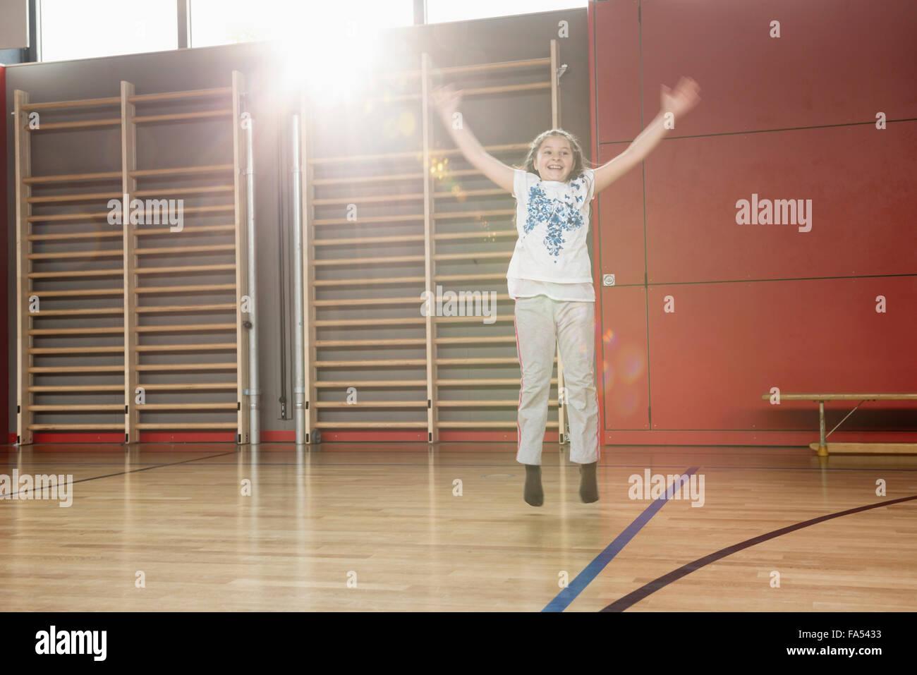 La pequeña niña alegre saltando en Sports Hall, Munich, Baviera, Alemania Imagen De Stock