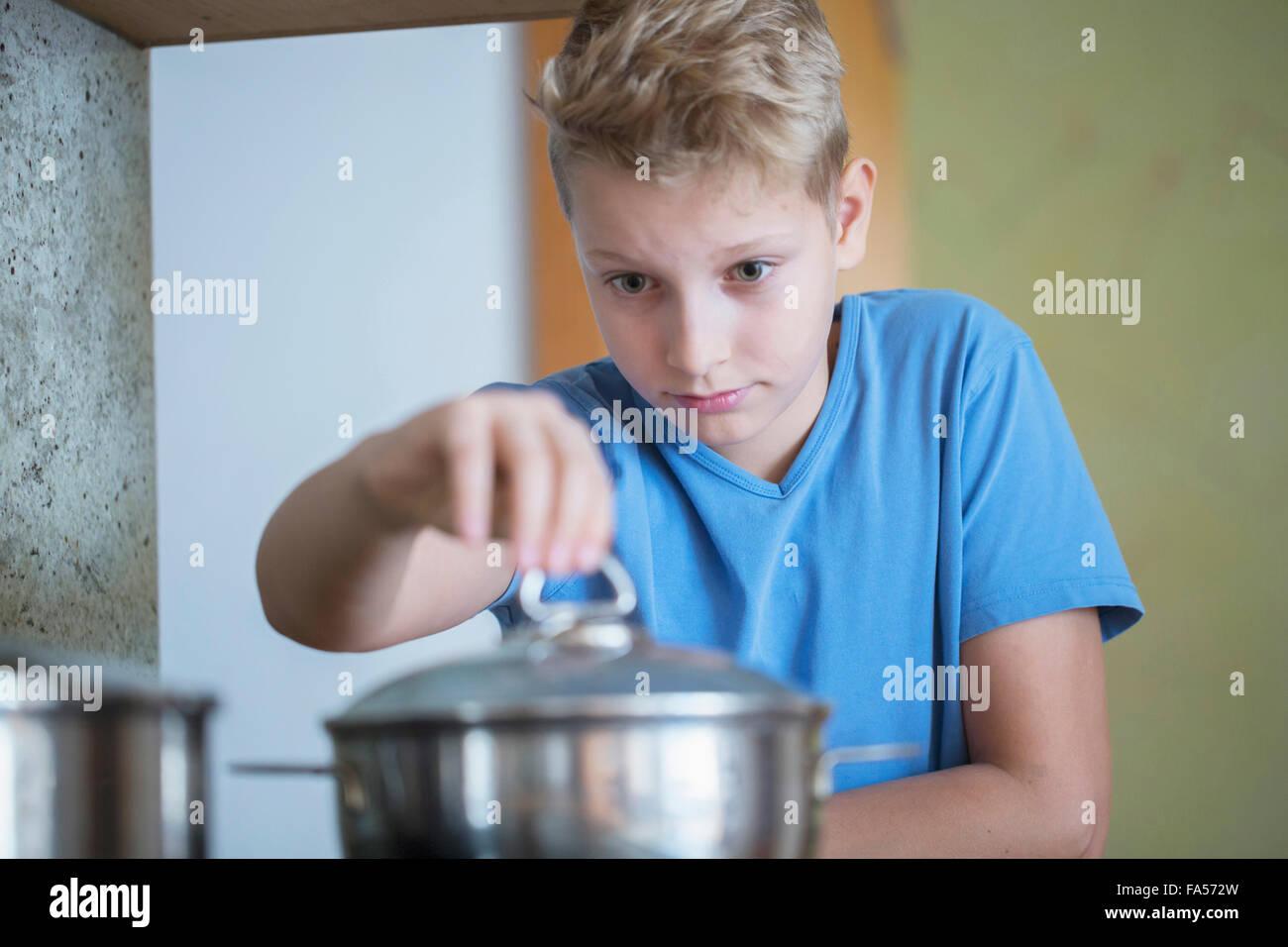 Tapa de apertura muchacho de sartén cuidadosamente, Friburgo de Brisgovia, Baden-Wurtemberg, Alemania Imagen De Stock