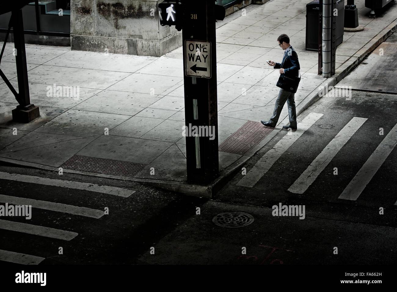 Un hombre que camina a través de un cruce de calle, mirando a un teléfono en su mano. Imagen De Stock