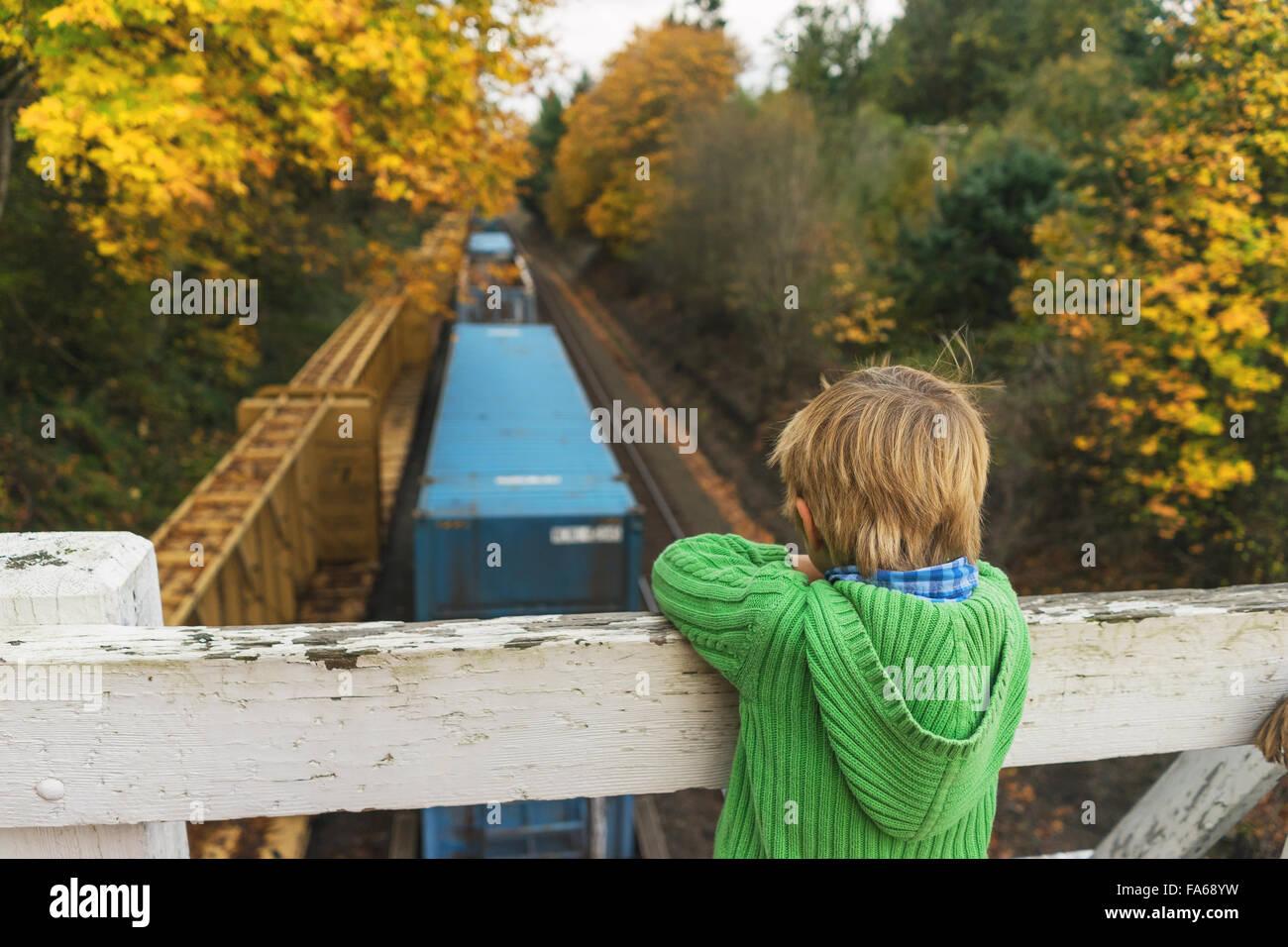 Chico busca en el puente permanente en tren por debajo Foto de stock
