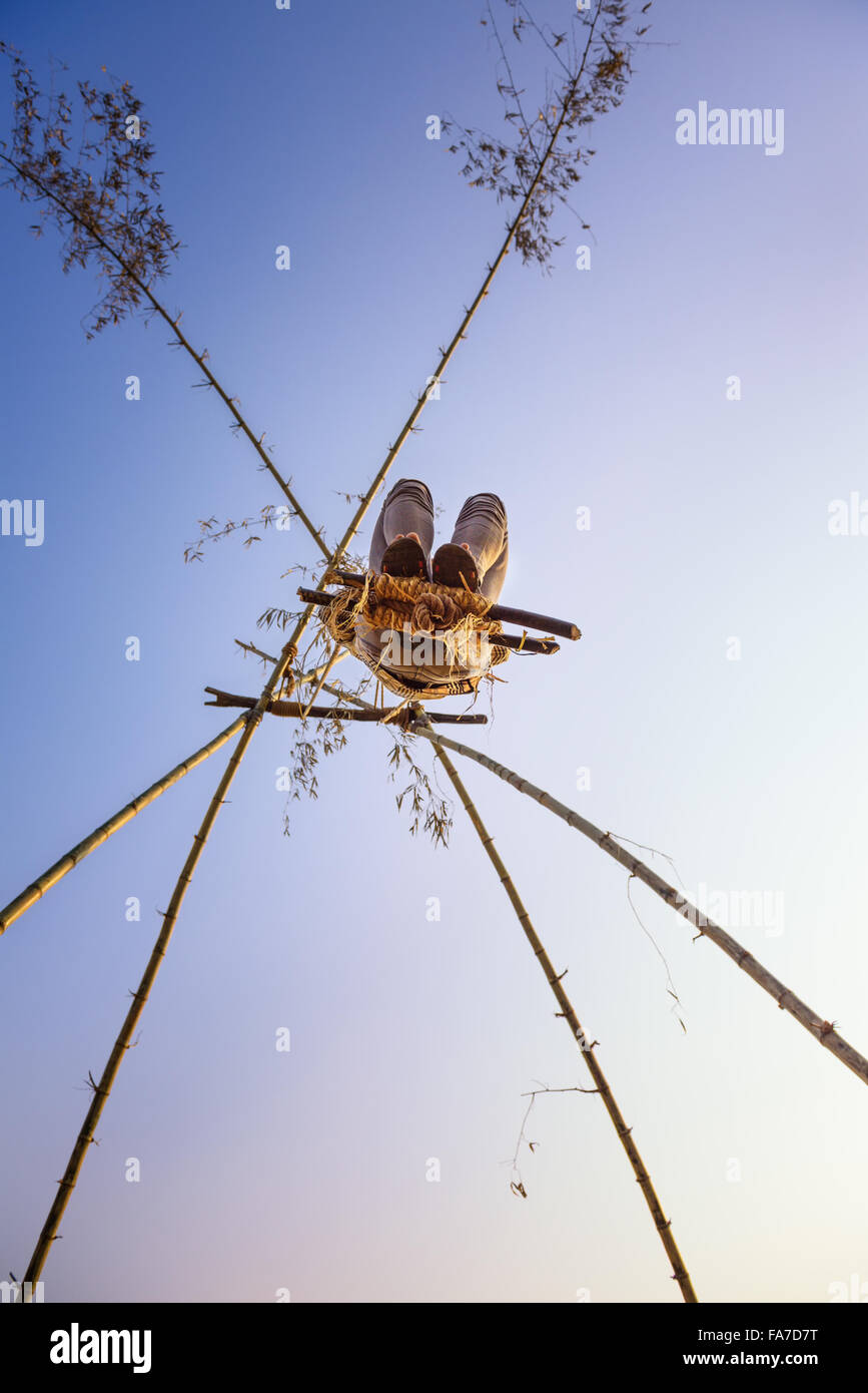 Joven jugando en un columpio de bambú tradicional llamado linge ping en Nepal Imagen De Stock
