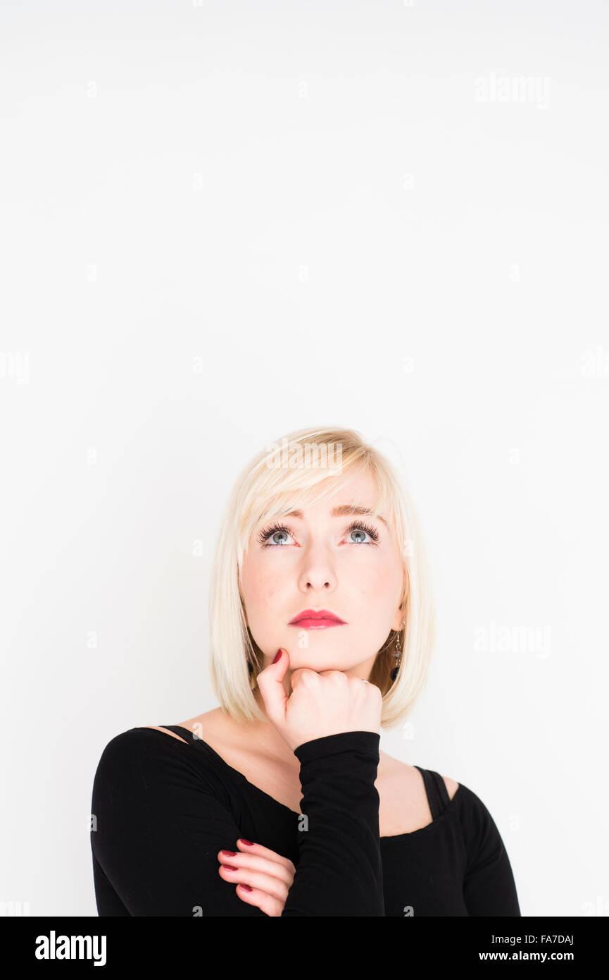 - Toma de decisiones y opciones de vida difícil: una joven mujer de pelo rubio rubio slim chica, pensando, Imagen De Stock