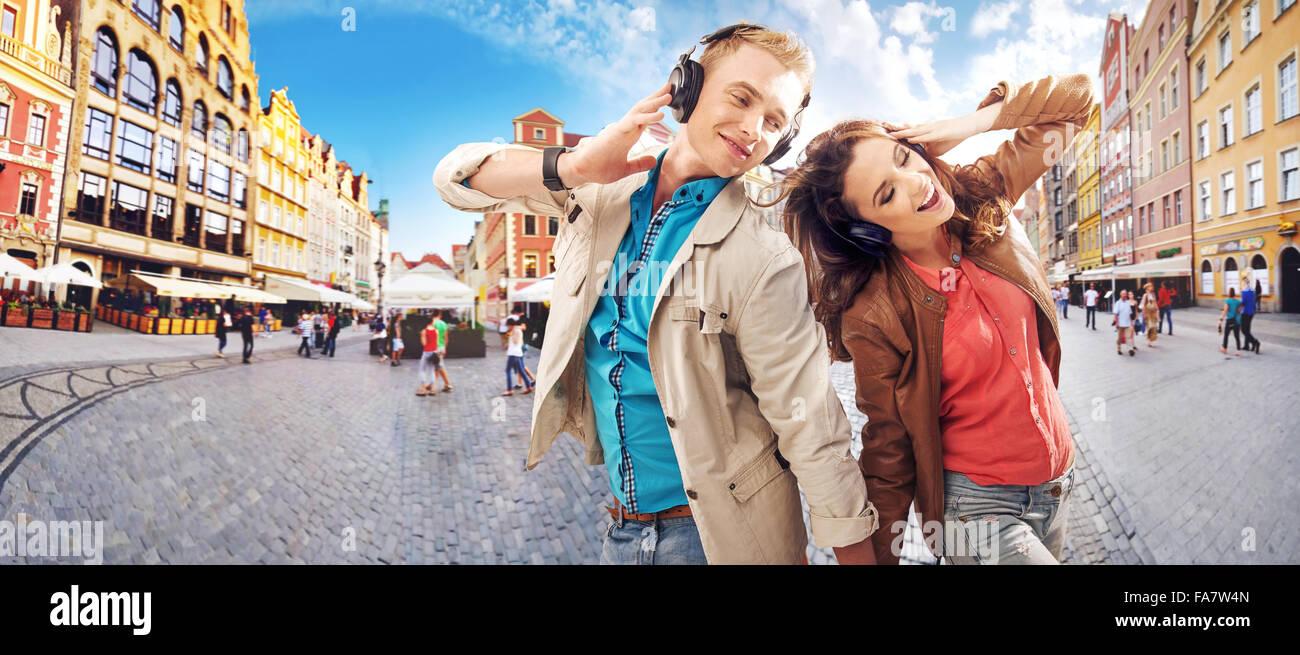 Pareja joven alegre escuchando música Imagen De Stock