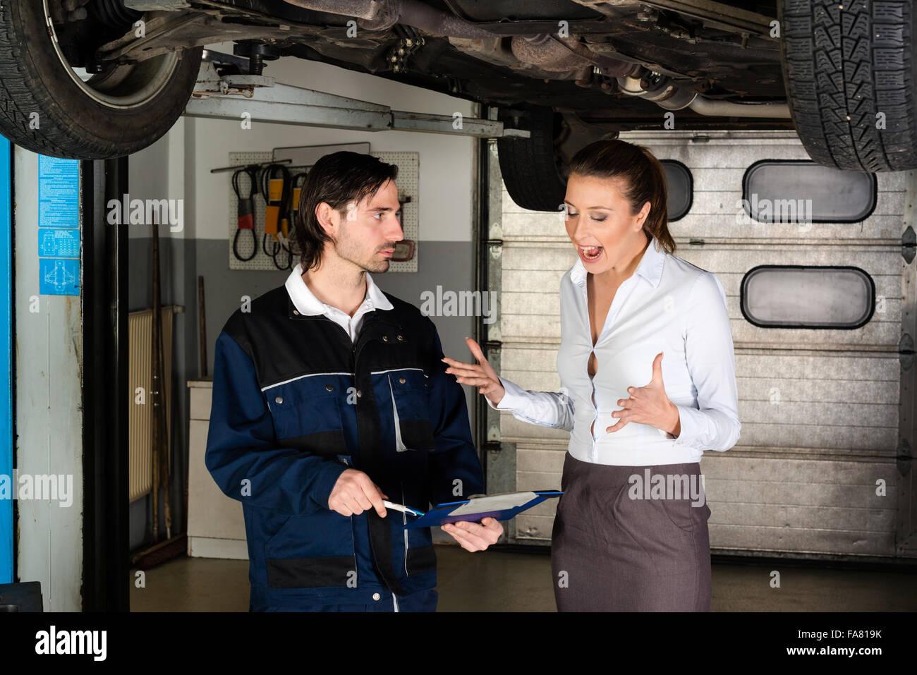 Mecánico de automóviles con enojado clienta Imagen De Stock
