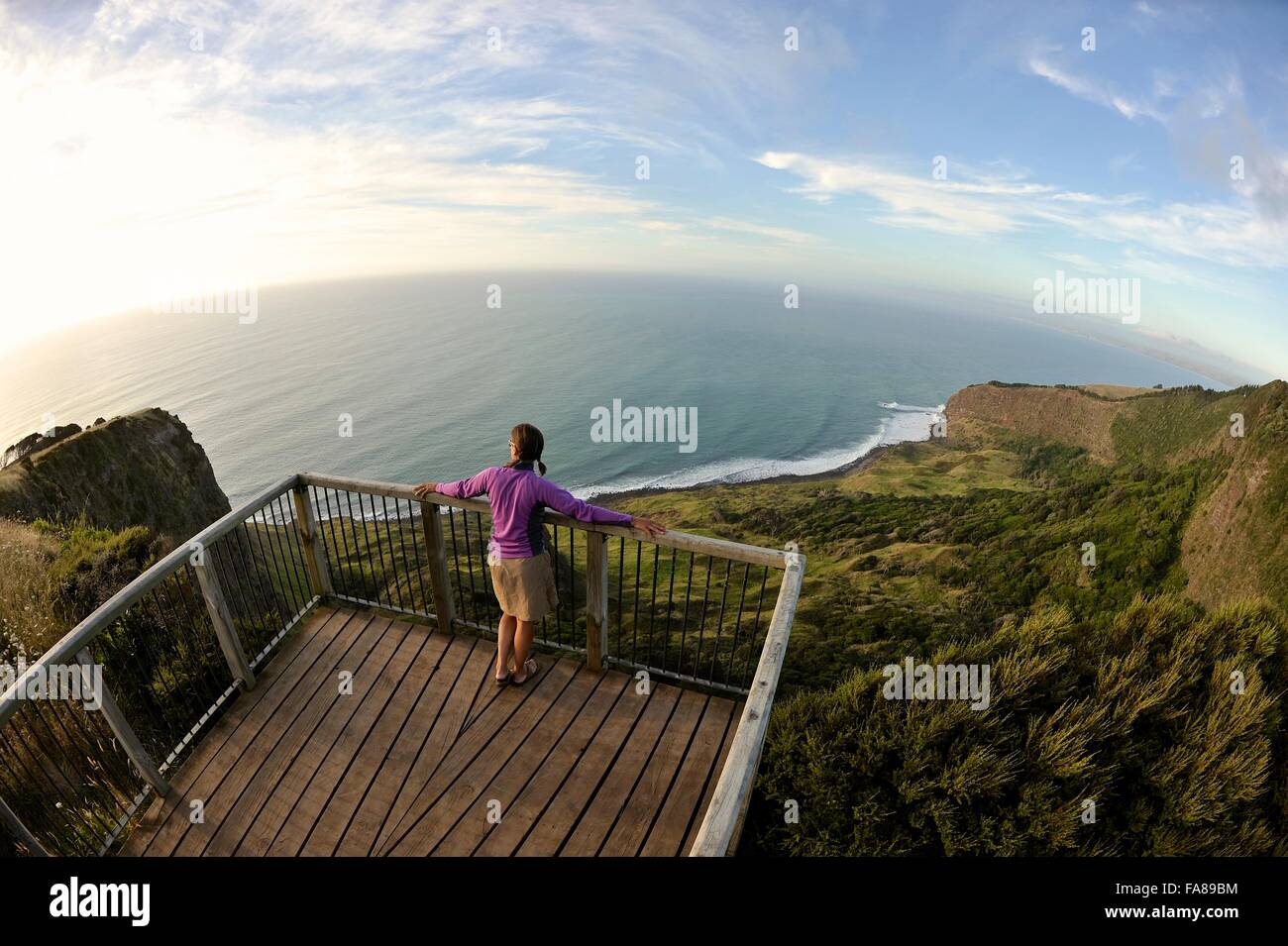 Un alto ángulo de visualización de la mujer joven mirando hacia la costa, Isla del Norte, Nueva Zelanda Foto de stock