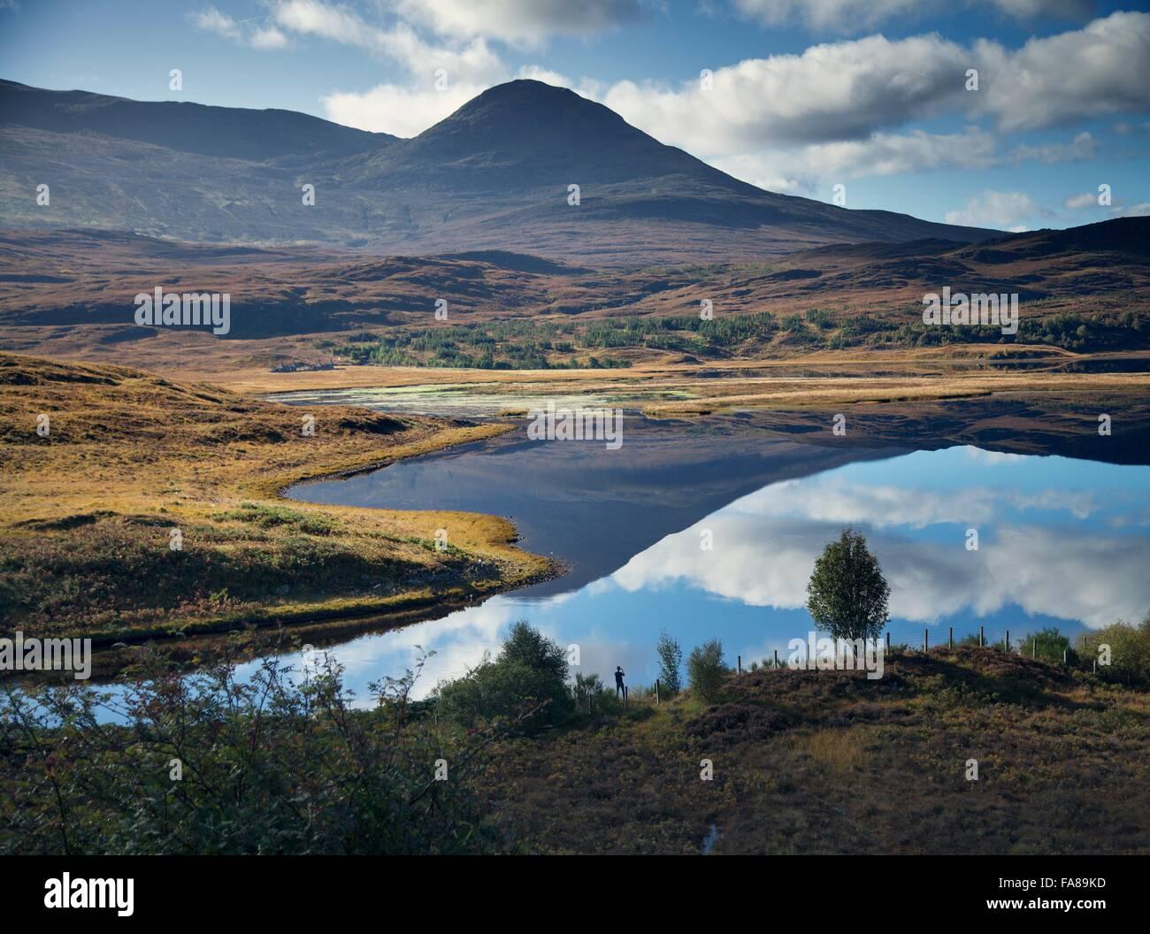 Hombre fotografiando reflejo de montaña en loch, Highland, Escocia Foto de stock